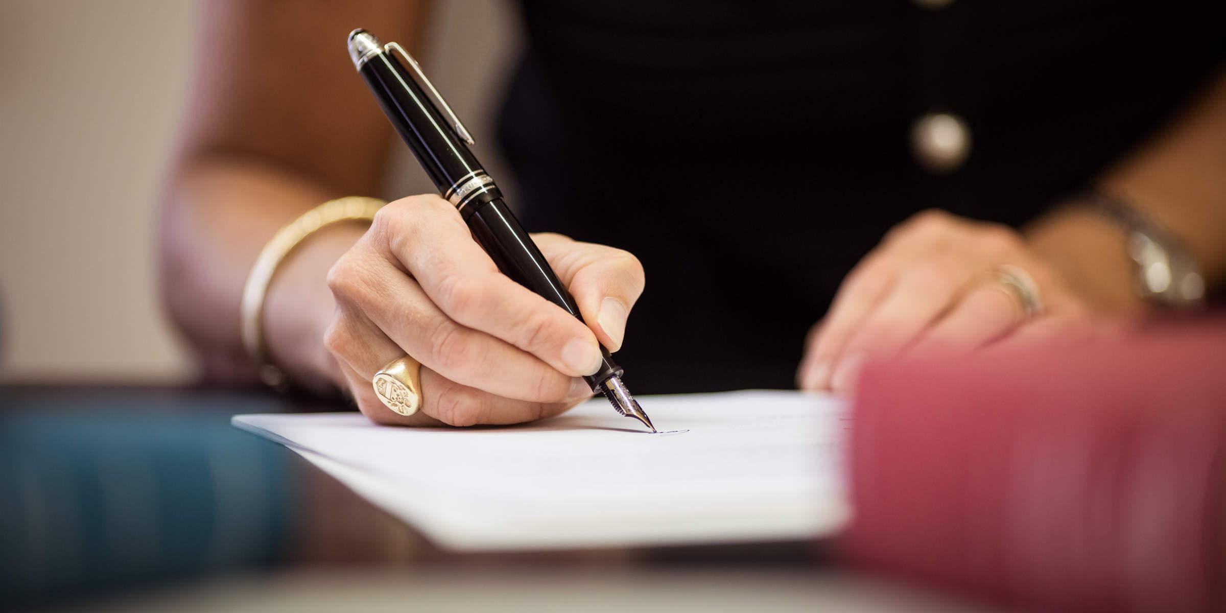 Rechtsanwältin Pagliarin verfasst ein Vertragsdokument am Schreibtisch