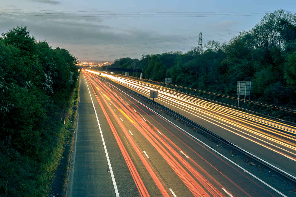 Foto Autobahn bei Dämmerung mit Lichtstreifen - bildlich für Transportrecht in Europa