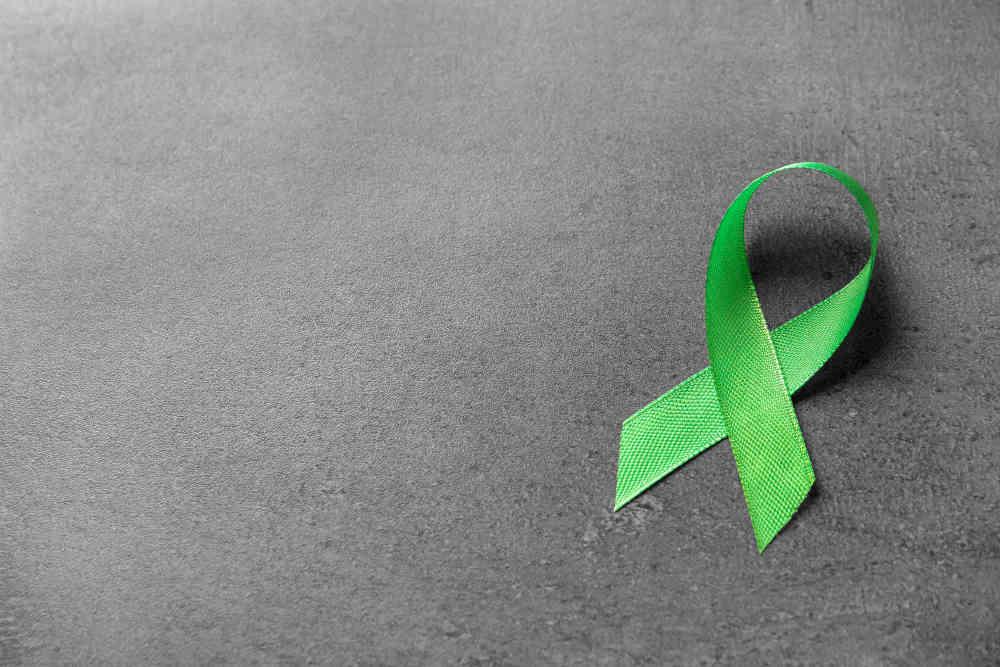Grüne Schleife auf Steinplatte - Symbol für seelische Gesundheit